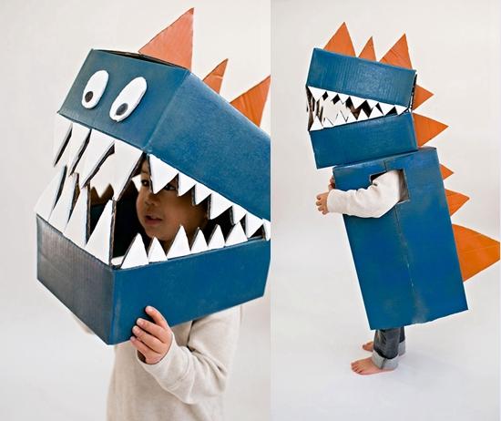 给纸盒上色,粘上锯齿形的牙齿来做出一个恐龙式的头盔,而纸箱上色,剪